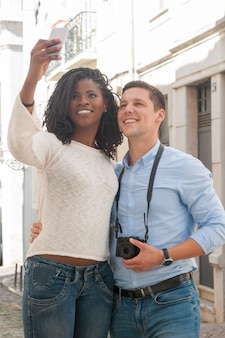 Positive interracial couple taking selfie photo outdoors