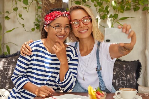 ポジティブな異人種間の女性はテーブルに座っている間抱擁します