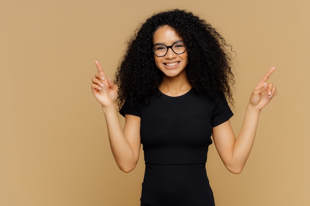 Позитивная радостная женская модель указывает вверху, показывает что-то вверх, имеет дружеское радостное выражение