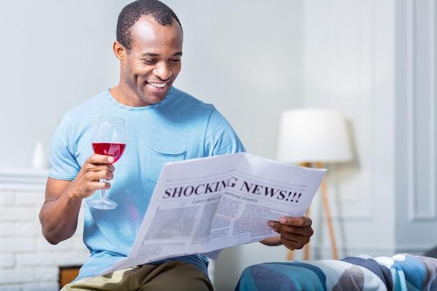 신문을 읽는 동안 웃고 와인을 마시는 긍정적 인 즐거운 행복한 사람