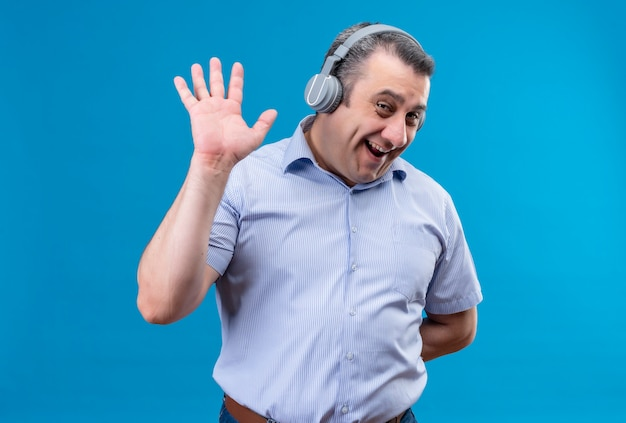 Positive and joyful middle age man in blue striped shirt wearing headphones showing high five gesture on a blue background