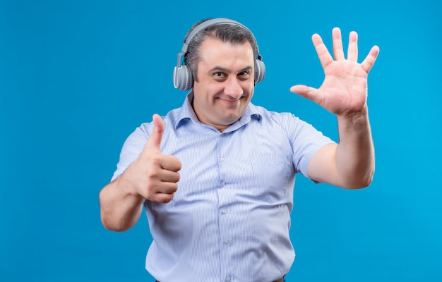 Positive and joyful middle age man in blue striped shirt wearing headphones showing with fingers number six on a blue background