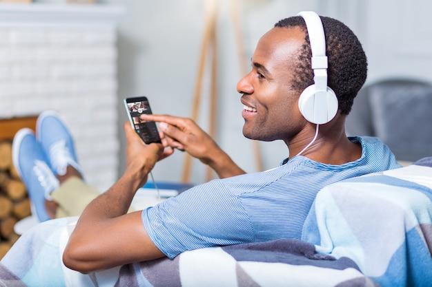 Позитивный радостный приятный мужчина улыбается и нажимает на экран своего смартфона, отдыхая дома