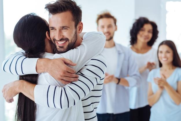一緒に立っている間、笑顔で抱き合っているポジティブで楽しい素敵な人々