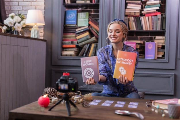 Positive joyful woman holding two books while showing them to the camera