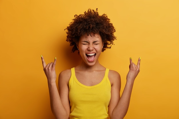 La donna gioiosa positiva fa il segno dell'heavy metal, si diverte al festival di musica a dondolo, esclama ad alta voce, chiude gli occhi, gesticola attivamente, vestita con abiti casual, isolata su un muro giallo. rock n roll baby
