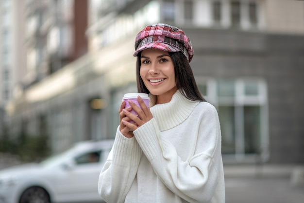 Положительная радостная женщина улыбается, держа чашку с кофе