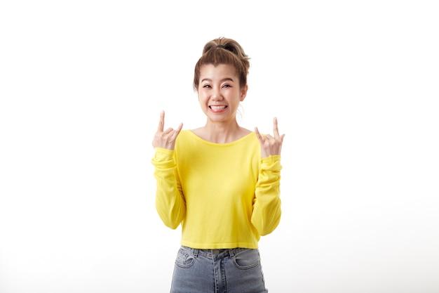 短い髪のポジティブな楽しい女性は、マスタードのプルオーバーを着てヘビーメタルのサインを作ります