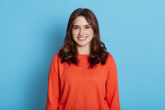 Positive joyful young beautiful female with dark hair wearing casual clothing, looking  and pleasantly smiling, wearing orange sweater, standing isolated over blue wall.