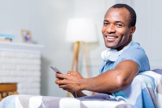 Позитивный радостный молодой человек улыбается и смотрит на вас, используя свой гаджет