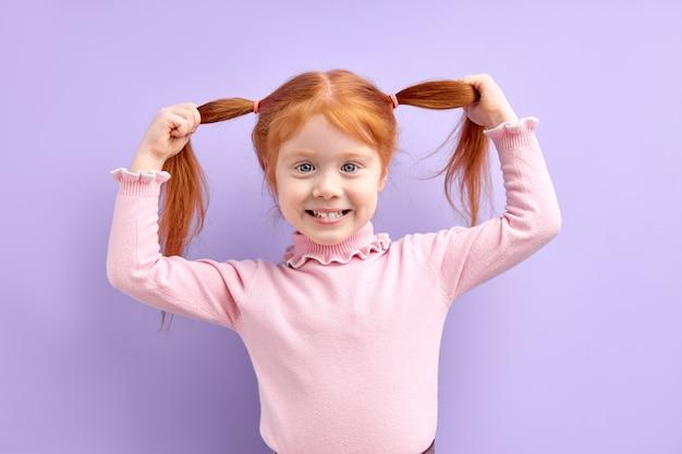 ポジティブな子供の女の子は手に2つの尾を持って楽しんでいます