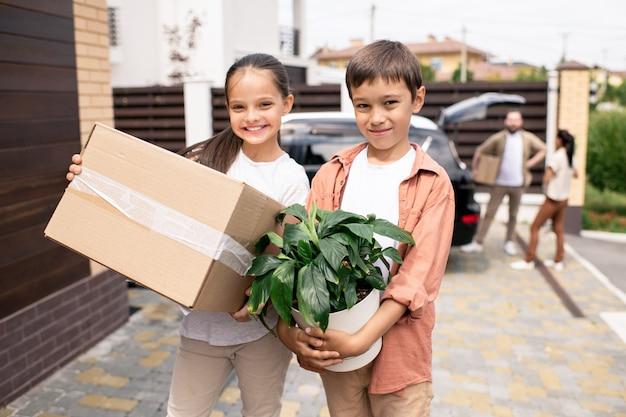 植物と箱を持つポジティブな子供たち