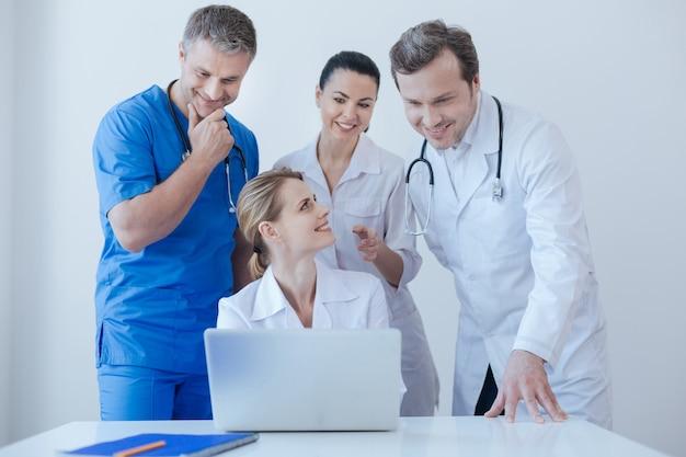会話を楽しみ、意見を共有しながら、病院でデジタルラップトップを使用して作業している前向きな親切な発明家