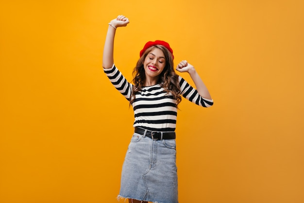 Positive lady in beret and shirt smiling on orange background. stylish woman in good mood with wavy hair dancing on isolated backdrop.