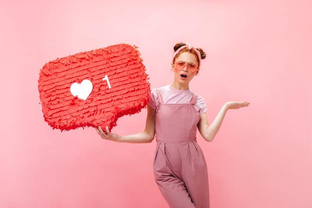 ピンクのオーバーオール、tシャツ、ピンクのアクセサリーに身を包んだポジティブな女性は、同じようなサインを指さします。