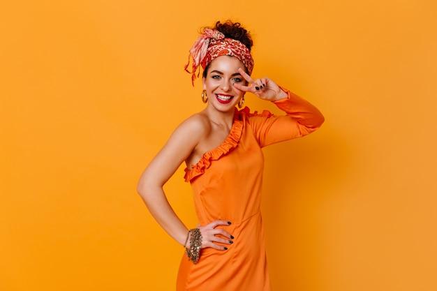 주황색 우아한 드레스와 세련된 머리띠의 긍정적 인 여성은 진심으로 미소 짓고 주황색 공간에 평화 기호를 보여줍니다.