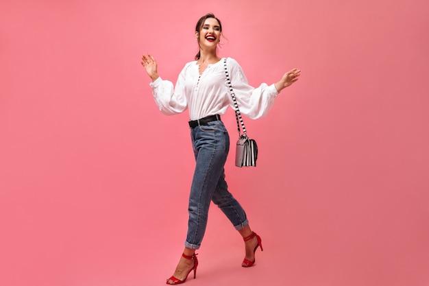 ハンドバッグでスタイリッシュな衣装のポーズでポジティブな女性。赤い口紅と縞模様のバッグを持つ笑顔の女性は、孤立した背景に移動します。 。