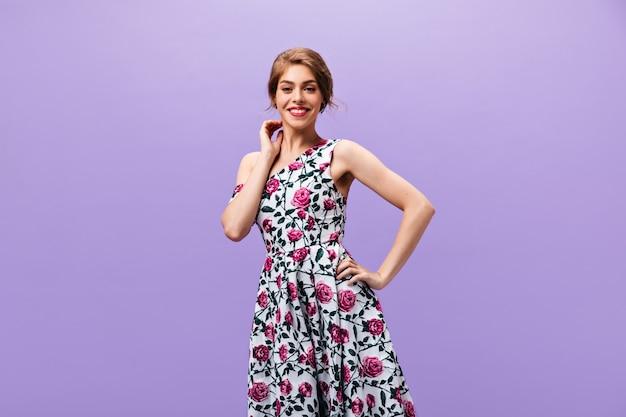 보라색 배경에 유행 드레스 미소에 긍정적 인 아가씨. 카메라에 포즈 꽃 세련 된 옷에 멋진 물결 모양의 머리 여자.