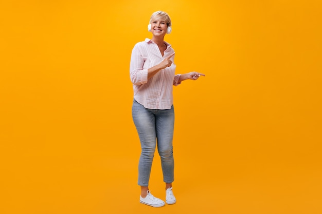Positive lady in jeans and shirt dancing and listening to music in headphones