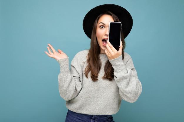 Позитивная студентка в черной шляпе и сером свитере с мобильным телефоном