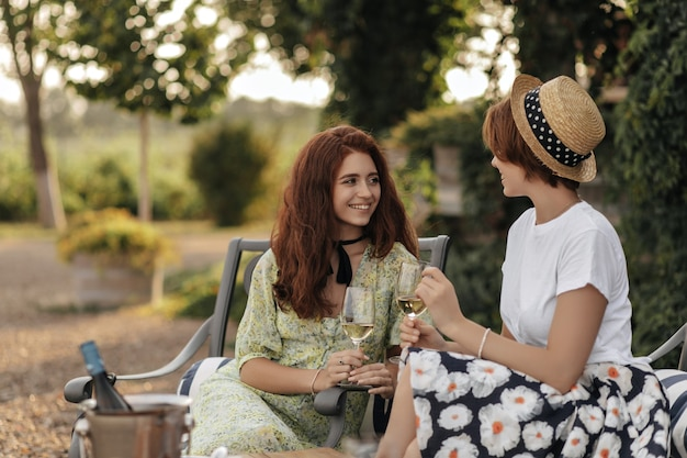 Positive lady with ginger hair in stylish clothes holding glass with wine sitting on chair with short haired girl in white t-shirt outdoor