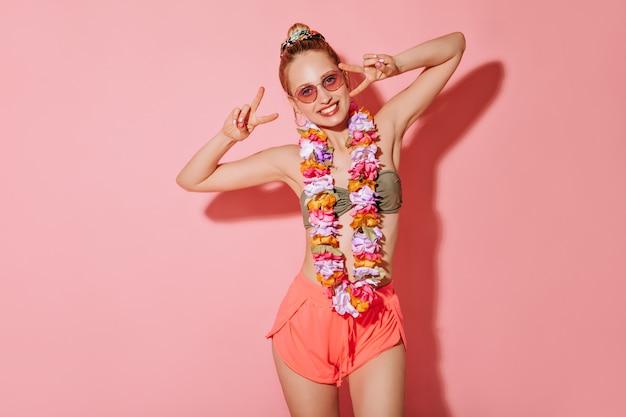 둥근 귀걸이와 수영복, 반바지와 꽃의 목걸이에 분홍색 sunglases가있는 긍정적 인 아가씨와 격리 된 벽에 평화 기호를 보여주는 꽃