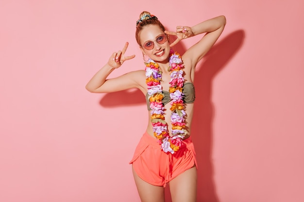 Positive lady with round earrings and pink sunglases in swimsuit, shorts and necklace of flowers smiling and showing peace sign on isolated wall