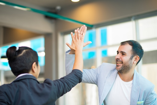 Positive latin and asian managers high fiving