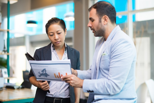 Positive latin man showing report to asian woman with folder