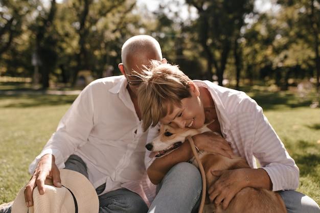 笑顔、コーギーを抱き締め、公園で白いモダンなシャツを着た男とポーズをとって、ストライプのシャツを着たブロンドの髪でポジティブな横たわっていた。