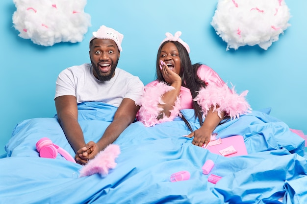 Positive lazy afro american family couple pose in bed under blanket have cheerful expressions enjoy weekend together surrounded with different items isolated on blue