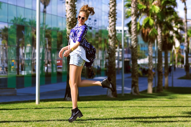 Positive lifestyle fashion portrait pf happy joyful woman jumping and dancing at park in barcelona, enjoy her travel vacation, bright trendy clothes and sunglasses, happiness, emotions.