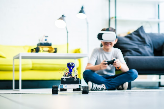 Positive little boy using vr glasses while using a remote control to test the robot