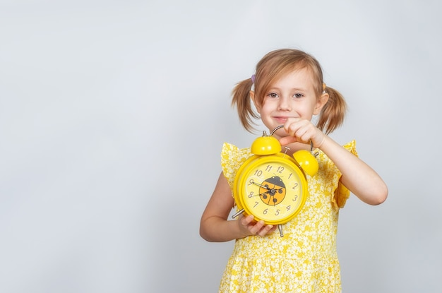 A positive little caucasian girl holds an alarm clock in her hand and smiles