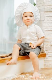 台所のテーブルに座っているクックスーツを着たポジティブな小さな魅力的な白人の男の子