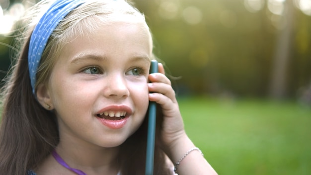 夏の公園で彼女の携帯電話で会話をしているポジティブな小さな子供の女の子。