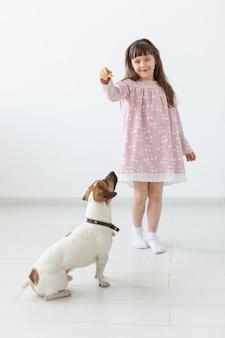 ピンクのドレスを着たポジティブな少女が、白い壁で小さな犬のジャックラッセルテリアを遊んで餌を与えています。好きな動物や犬のコンセプト。コピースペース。