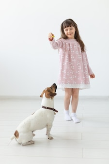 Positive little girl in a pink dress playing and feeding her little dog jack russell terrier on a white wall. the concept of favorite animals and dogs. copyspace.