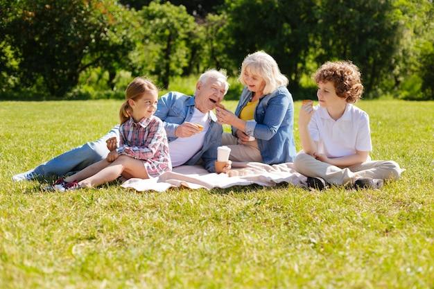 Позитивная маленькая девочка сидит на пледе рядом с бабушкой и дедушкой и держит торт, глядя на своего брата