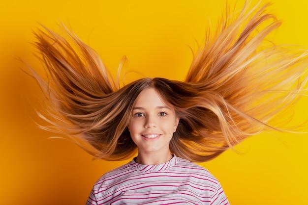 Позитивная маленькая девочка со светлыми волосами, летящими на желтом фоне