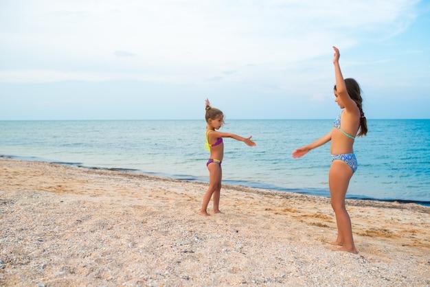 ポジティブな女の子の姉妹は、晴れた暖かい夏の日の夏休み中に砂浜でアクティブなゲームをします。冬と街からの休息の概念