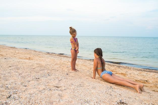 ポジティブな小さな女の子の姉妹は、晴れた暖かい夏の日の夏休み中に砂浜でアクティブなゲームをプレイします
