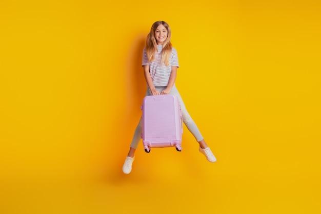 Позитивная маленькая девочка, изолированная на желтом фоне, прыгает, удерживает чемодан