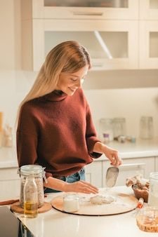 Positive long haired woman standing in the kitchen and smiling while sifting flour on the dough
