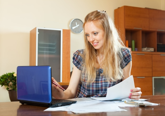 Positive long-haired woman working with documents and laptop