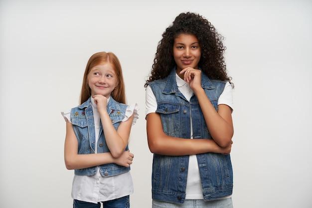 긍정적 인 장발 젊은 숙녀들은 캐주얼 한 옷을 입고 흰색 포즈를 취하면서 진심으로 웃고, 즐거운 감정을 보여주는 동안 제기 된 손에 턱을 기울입니다.