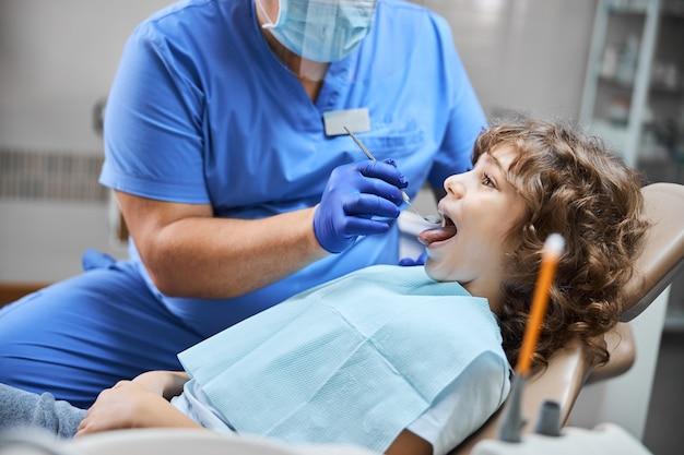 치아가 충치와 충치를 검사하는 동안 웃고있는 긍정적 인 아이