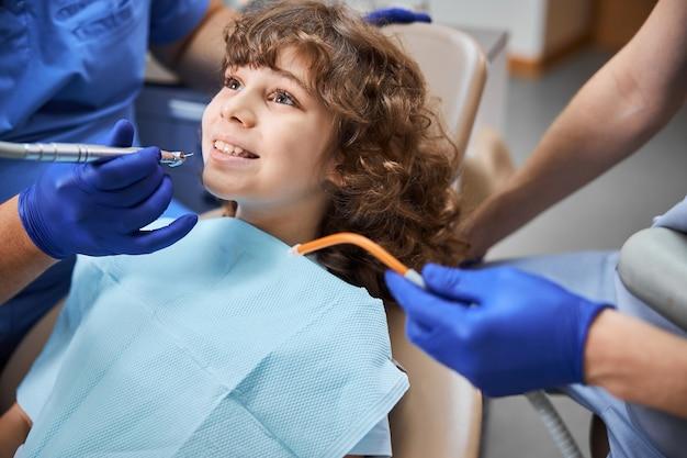 歯科医に歯を治療されている歯科医院に座っている間、大きく笑っている前向きな巻き毛の子供