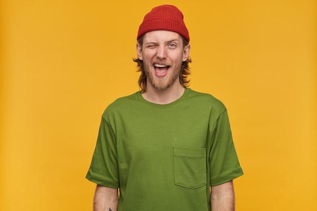 Позитивно выглядящий мужчина, красивый бородатый парень со светлыми волосами. в зеленой футболке и красной шапке. имеет татуировку. изолированные над желтой стеной