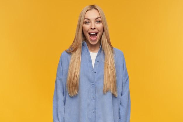 ポジティブな女性、長いブロンドの髪を持つ陽気な女の子。青いシャツを着ています。人と感情の概念。大まかに笑っている。オレンジ色の背景の上に分離されたカメラで見て